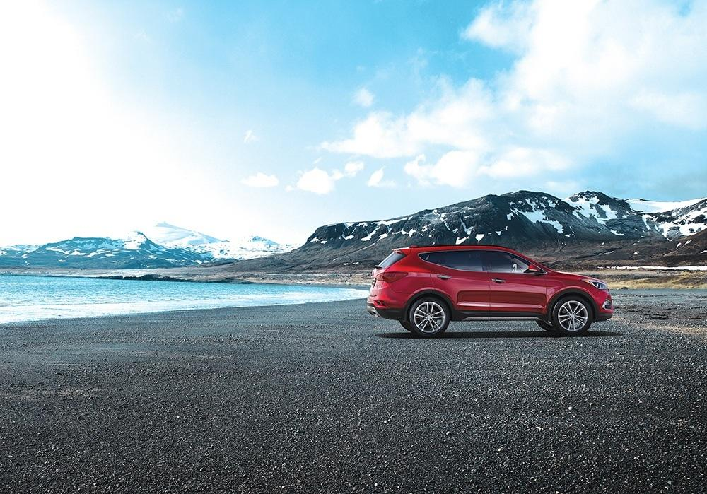A red Hyundai Santa Fe parked on asphalt next to a blue lake in front of some snowy mountains.