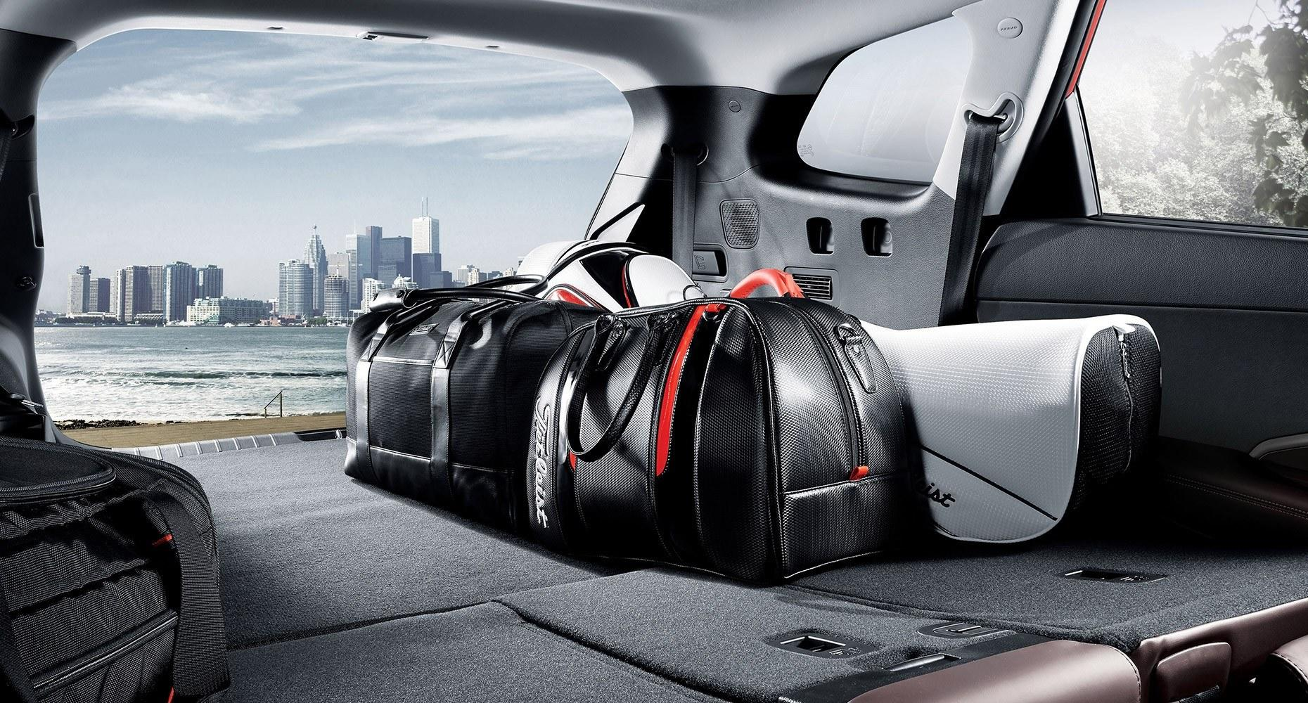 An interior shot of a Hyundai SUV, looking through the open rear door at a city skyline across a river. Some bags are stowed on top of folded-down rear seats.